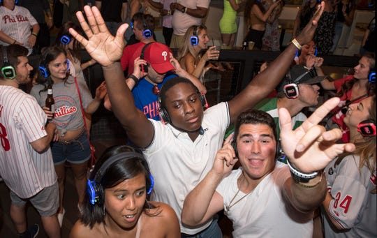 Partiers dance as they attend a silent disco party at 1100 Social, located in Xfinity Live! in Philadelphia, on Friday, July 12, 2019.  A silent disco is an event where people dance while listening to music on wireless headphones.