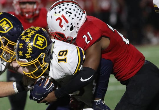 La Salle's Jaylen Johnson (21) tackles  Moeller's  Carrington Valentine (19) during their football game, Friday, Sept 28, 2018.