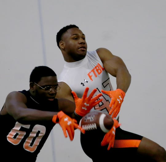 La Salle running back Cam Porter tries to catch a pass in front of Tim Pennington (60) during the Under Armor All American Camp in Cincinnati, Sunday, April 14, 2019.