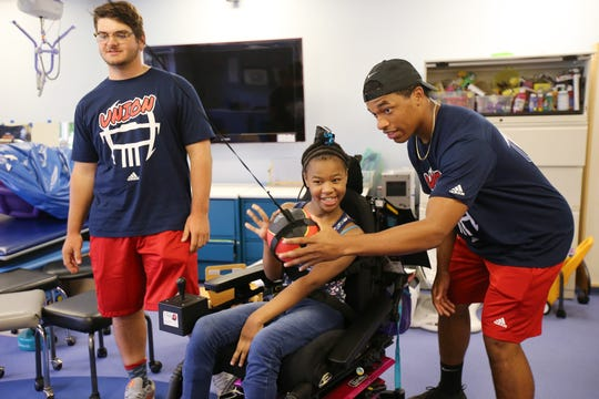 Hunter Timpson, 18, of Summit and Ernesto Hernandez, 19, of Union play a game with Keyziah Coesmith, 12, of Mountainside as cheerleaders and football players, who will be participating in the Autoland Classic all-star football game, visit with residents in the long term care unit at Children's Specialized Hospital in Mountainside, NJ Monday July 15, 2019.