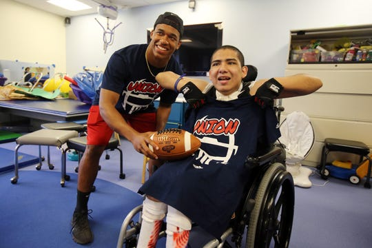 Ernesto Hernandez, 19, of Union gives Joffre Suarez, 19, of Mountainside a game t-shirt as cheerleaders and football players, who will be participating in the Autoland Classic all-star football game, visit with residents in the long term care unit at Children's Specialized Hospital in Mountainside, NJ Monday July 15, 2019.