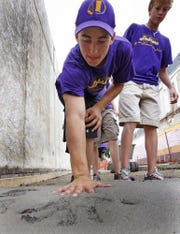 Dobbers Up baseball team member Matt Mitchell, 14, of Indianola, puts his hand in cement during RAGBRAI's last stop in Indianola in 2009.