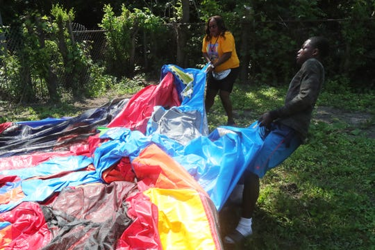 Toriahna Bonds (left) is the owner of a bounce house business called Jumping J's. She and her assistant, Jelani Parker, set up tents and a bounce house for a party in Detroit on Sat., July 13, 2019.