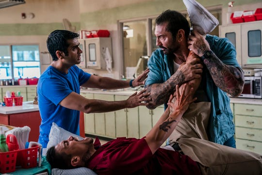 "Dave Bautista, right, and Kumail Nanjiani, standing left, in a scene from ""Stuber."""