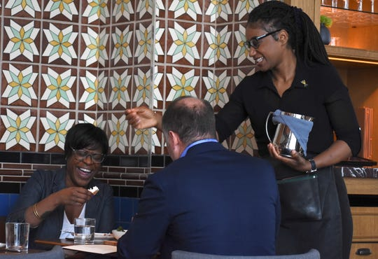 (Left to right) Jamila Thompson, of Detroit, shares a laughter-filled lunch with Troy Larson, of Birmingham, as server Tahirah Muhammad gets in on the fun.