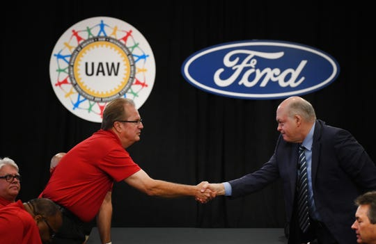 FILE - UAW President Gary Jones and Jim Hackett, President and CEO of Ford Motor Company, shaking hands, at the start of contract negotiations.