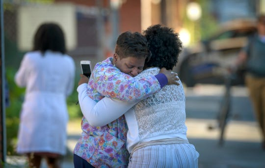Two women embrace in an alley behind the Man Alive drug treatment center in Baltimore shortly after a shooting. At least two people are dead and a police sergeant and a woman are injured following a shooting at a methadone clinic in Baltimore, police said Monday.