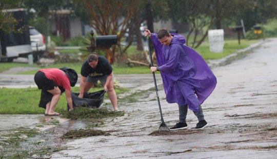 Joni Giandelone, foreground, rakes in the pine needles and branches deposited from Tropical Storm Barry, in front of her house with the help of Priscilla Percle, center, and her mother Gayle Percle in Morgan City, La., Saturday, July 13, 2019.