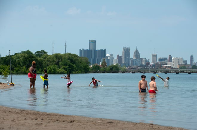 With mid-summer temperatures in the upper 80's, people escape the heat while splashing in the Detroit River at the beach on Belle Isle.