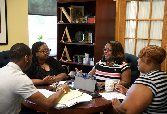 ​Detroit NAACP chapter executive director Kamilia Landrum, second from right, prepares her welcome remarks for the convention book with, from left, executive assistant Jermaine Peguese, public relations and communications manager LaToya Henry and volunteer Star Edison, far right, at the Detroit NAACP office in Detroit on Monday.