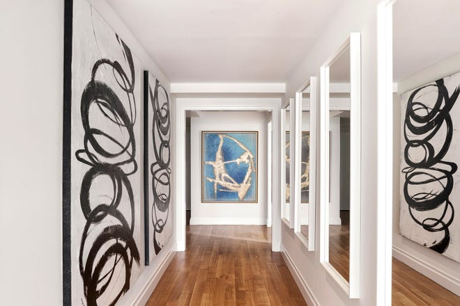 Inexpensive mirrors purchased from a bargain store hung in a series elongate this hallway.