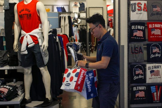 A man buys clothes from an American clothing store having a promotion sale at a shopping mall in Beijing on Monday.