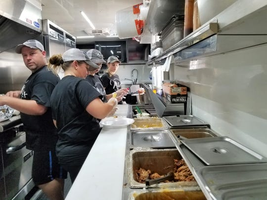 Warren Miller, left, with wife Dianna, sister-in-law Elaine Staley and daughter Charli work inside the well-equipped Miller's Barbecue trailer in July, 2019.