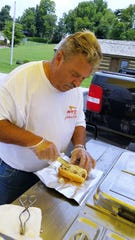 Gerald Bowser assembles a hot dog at his Dawgs on the Ohio cart, July 2019.