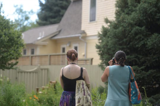 Historic preservation specialist Reyana Jones, right, photographs a designated local landmark home Wednesday as historic preservation intern Delaney Taylor, left, looks on.
