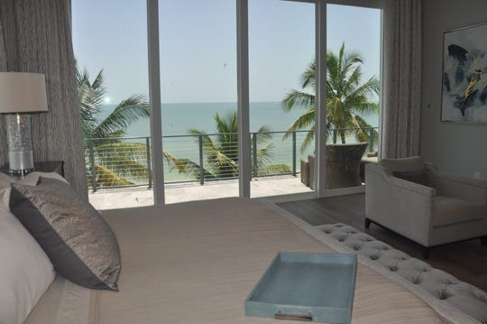 The Gulf and beach can be seen through the sliding glass doors in the master suite.