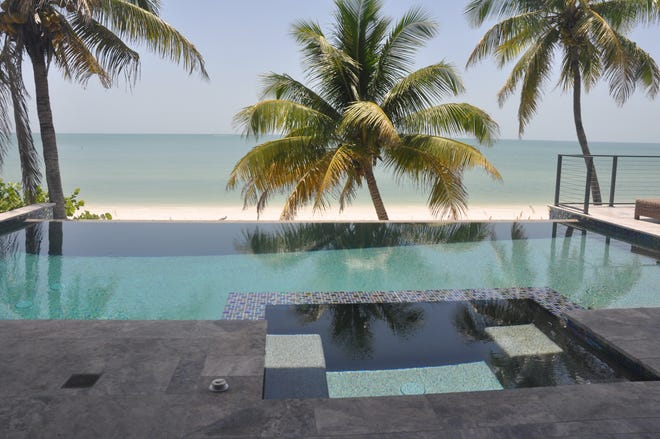 The infinity edge pool located on the second level seems to flow right to the beach.