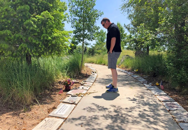 In his June 3, 2019 photo, Bill Arsenault of the Idaho Falls Fire Department looks at memorial stones at the Wildland Firefighters Monument at the National Interagency Fire Center in Boise, Idaho. Federal officials at the NIFC are bolstering mental health resources for wildland firefighters following an apparent increase in suicides.