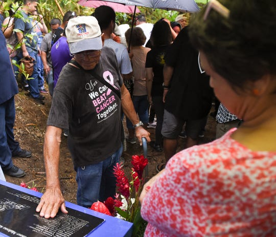 Gov. Lou Leon Guerrero observes as war survivor Jesus Reyes Garrido, 83, pays respects to the memory of his father, Ramon Garrido Garrido, at the Tinta massacre site in Merizo on July 15, 2019.