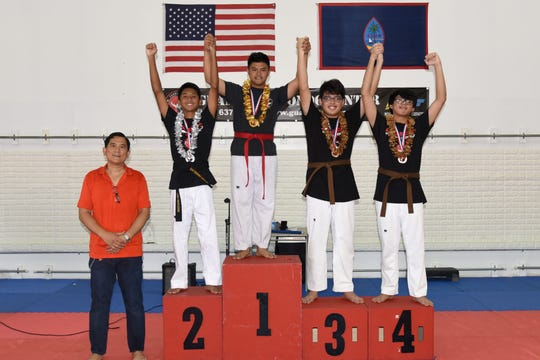 Master Noly Caluag, left, chief instructor of Guam Taekwondo Center, Inc. poses with the winners of men's division during the 1st Taekwondo Fitness Challenge held July 6, 2019.  Winners are:  1st Christom DelCarmen, 2nd James Echon, 3rd Emmanuel Velayo and 4th Elijah Velayo.