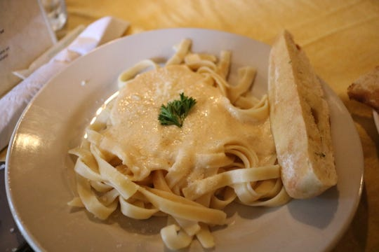 The fettuccine pasta lunch dish includes homemade sauce and a bread stick on the side.