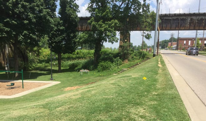 """There's a """"boardwalk"""" coming to this section of land above Sunset Park. It'll physically complete and connect the 2.6-mile Riverwalk and there will also be a seating area/overlook for checking out the Ohio River, the playground or trains as they roll by."""