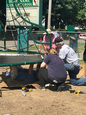 Parent volunteers and community members help install new playground equipment at Holy Name School. (Saturday, July 13, 2019).