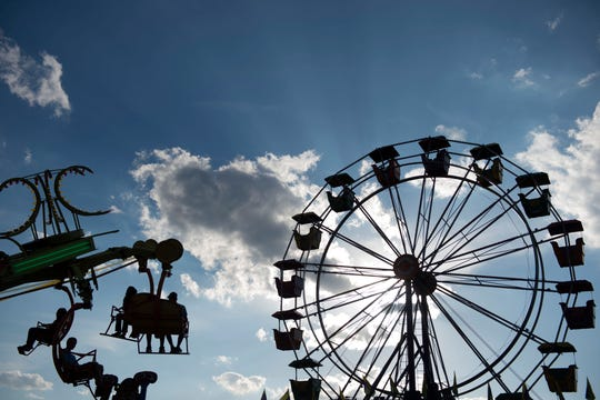 Patrons enjoy spinning rides at the Anderson County Fair in Clinton, Tenn., Tuesday, July 15, 2014.