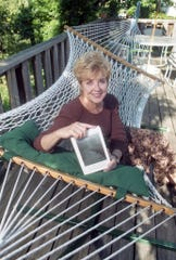 """Jeanne McDonald, editor of """"Voices from the Valley,"""" sits with her book on the patio of her home in West Knoxville in October 1994."""