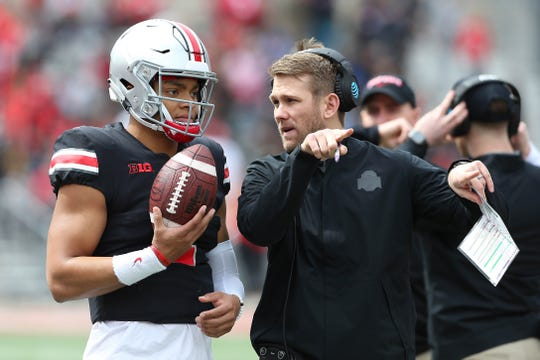 Quarterback Justin Fields gets advice from coach Corey Dennis during Ohio State's spring game.