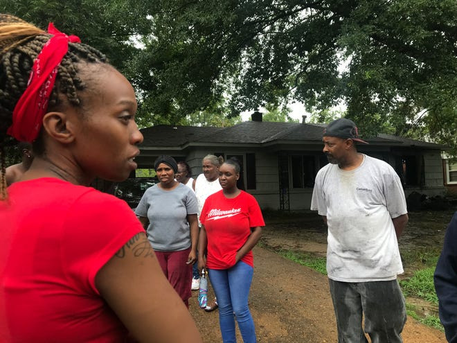 Rosalyn Crawford stands outside with family members at 4500 Willow Rd., after her house caught on fire with 5 children in the home.
