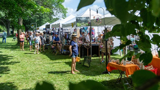 Visitors shop for unique handcrafted artwork during the Lake Country Art Festival at Naga-Waukee Park in Delafield on Saturday, July 13, 2019. The 2021 arts festival will take place July 10.