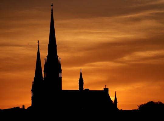 The sun sets behind St. John's Evangelical Lutheran Church, 804 W. Vliet St., in Milwaukee on Sunday. After a weekend of near normal temperatures, the following week is expected to be warmer.