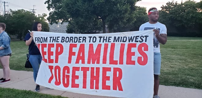 Gabriela Arevalo and Jean-Pierre Saint Louis hold up a banner during the Wauwatosa Lights for Liberty rally on July 12 near Wauwatosa City Hall, 7725 W. North Ave.