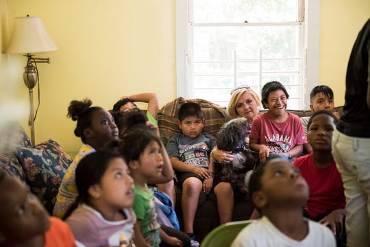 Rhonda Thompson hangs with kids as the do a bible study at the Nehemiah Center in Montgomery, Ala., on Monday, July 1, 2019.