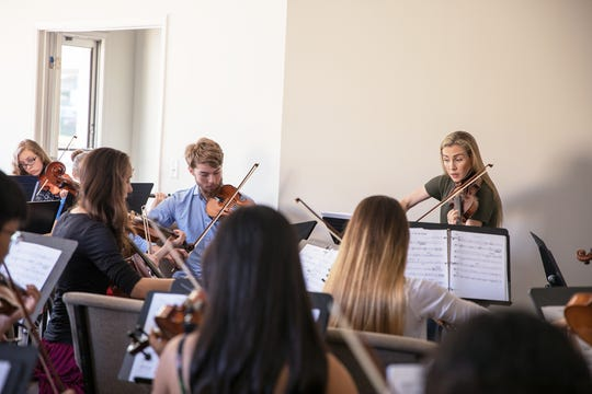 Annie Dupre, of the Annie Moses Band, leads an orchestra of student musicians.