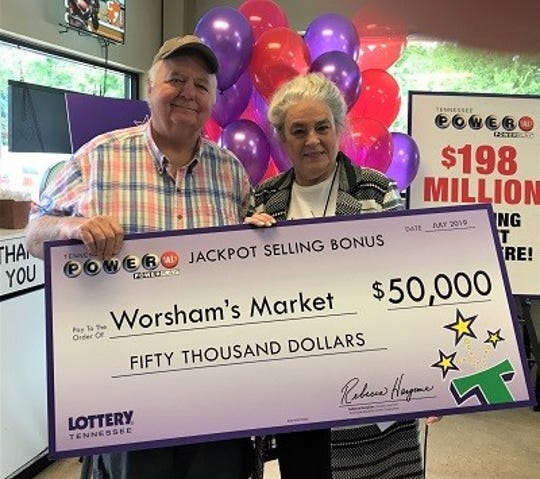 Worsham's Market owner Bob Worsham receives a check from the Tennessee Lottery Monday, July 15, 2019.