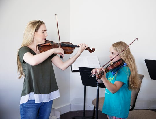 Annie Dupre instructs a student violinist as part of her work with the Annie Moses Foundation, named for her family's band.