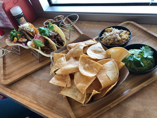 A meal from Turco Tacos including four tacos, an order of chips and guac and a serving of Mexican corn.