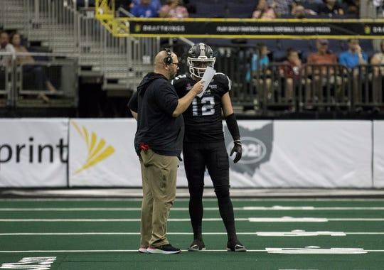 Newark's Grant Russell, quarterback for the Columbus Destroyers, gets a play from head coach Matthew Sauk Sunday in their Arena Football League game against Albany in Nationwide Arena.