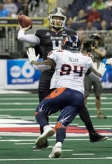 Albany defensive end Aaron Tiller (94), from Licking Heights and Southern University, rushes Columbus quarterback Liam Nadler Sunday during their Arena Football League game in Nationwide Arena.