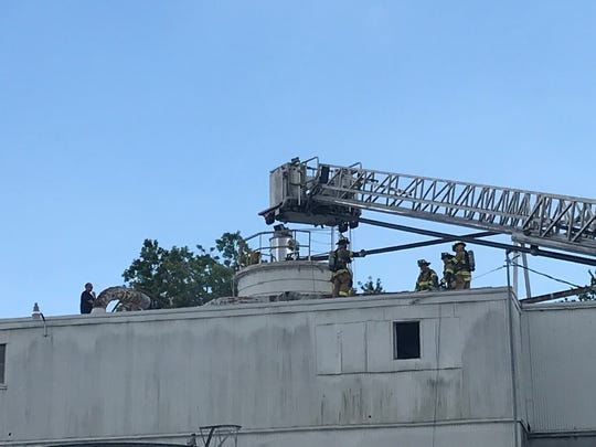 Licking County firefighters saw through a portion of the roof at Tectum Inc., a company in Newark, on Monday, July 15, 2019.