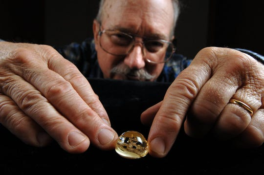 David Parris, curator of natural history at the New Jersey State Museum, shows the tiny Apollo 11 moon rocks, brought back 50 years ago from the first moon mission, encased in plastic. The rocks will be on display at the Trenton museum through Nov. 10.