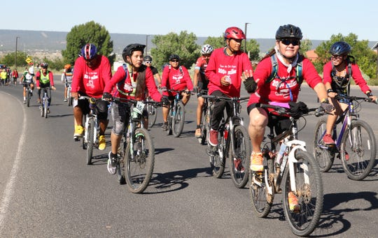 Part of the 2019 Tour de Sih Hasin Bike Ride move along the road to the Navajo Nation Council chamber on July 15 in Window Rock, Ariz.