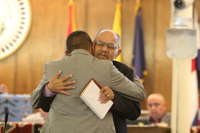 Delegate Nelson BeGaye, right, receives a hug from Delegate Pernell Halona during the Navajo Nation Council summer session on July 15 in Window Rock, Ariz. BeGaye resigned from the council, citing a health condition, on July 15.