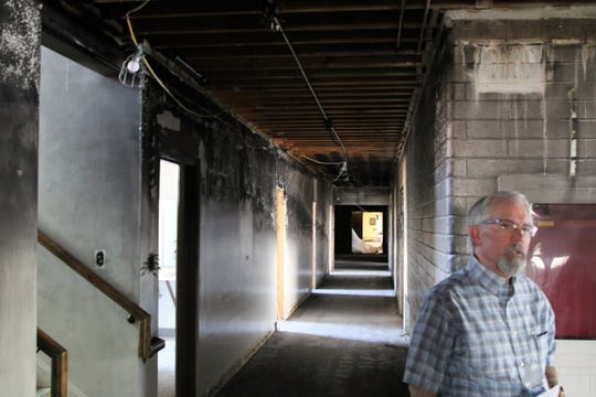 Seth Bingham, a spokesman for the Farmington stake, on July 15 stands in the hallway of  The Church of Jesus Christ of Latter-day Saints on West Apache Street that was scorched by fire on June 1 in Farmington.