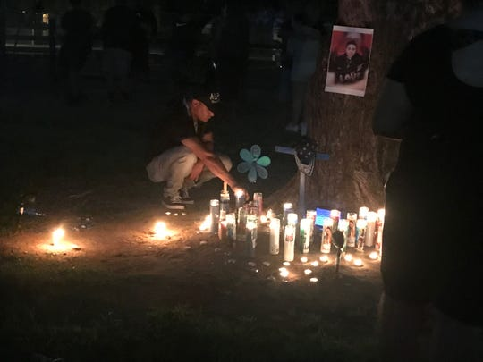 A friend lights candles at Nestor Lopez's Sunday night vigil on July 14, 2019.
