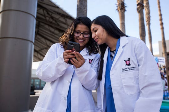 Senayda Perez (left) and Christine Torres take selfies next to their booth promoting the pharmacy program in 2018. South Mountain High School has four academies that focus on subjects like arts and engineering.