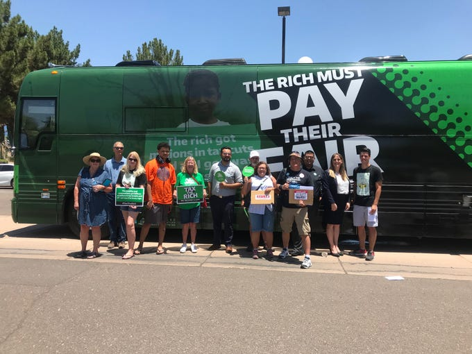 Speakers and activists gather for a photo in front of the tour bus.&nbsp;<br /> &nbsp;