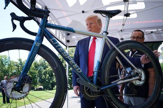 Trump observa una bicicleta fabricada en EEUU, con un valor de 13 mil dólares.